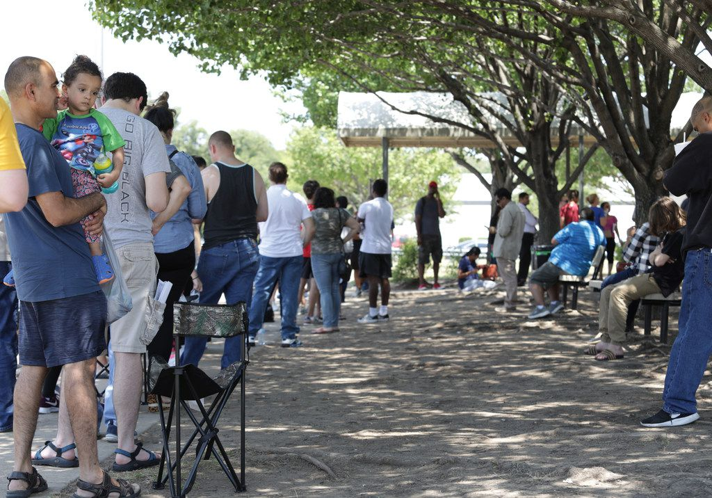 People wait outside in the summer heat at the Texas Department of Public Safety building in McKinney.