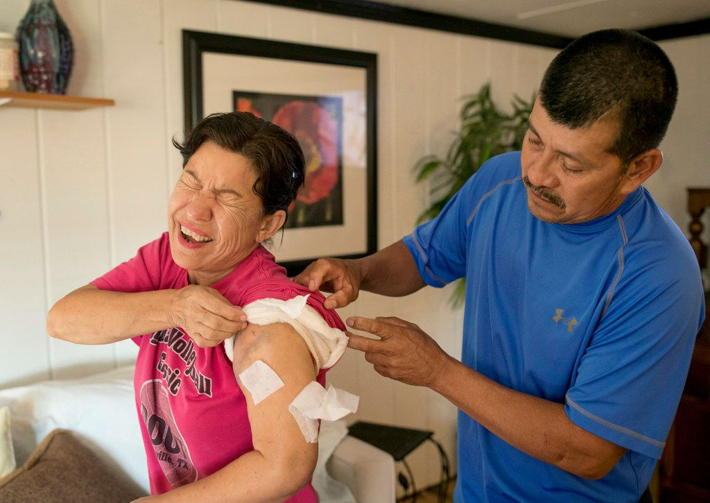 In this 2017 file photo, Joaquin Ramirez checks on the gunshot wound on Rosanne Solis' left arm at their home in Sutherland Springs.