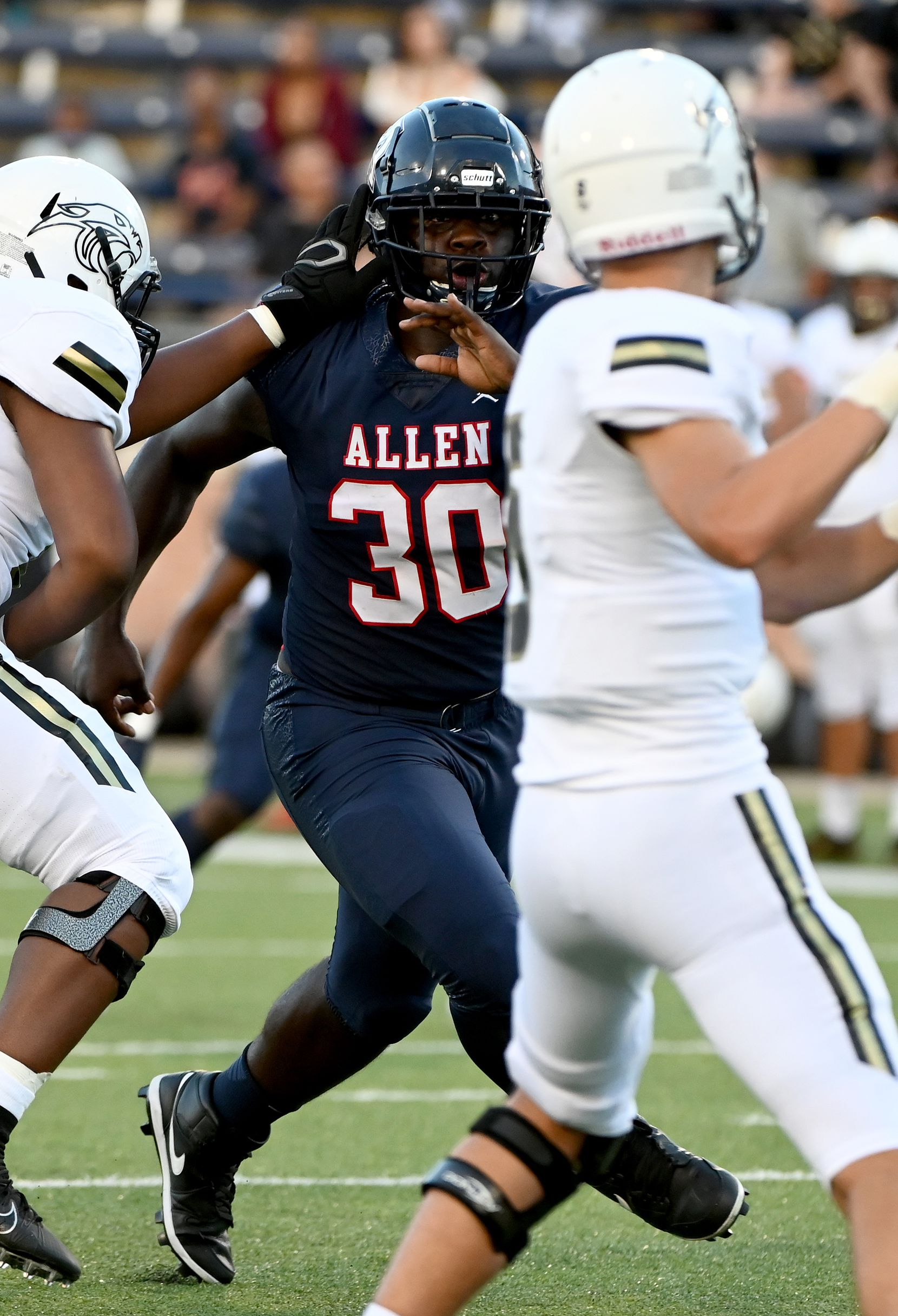 Allen's DJ Hicks (30) fights through a block by Plano East's Ralee Jackson as quarterback Drew Devillier looks to pass in the first half during a high school football game between Plano East and Allen, Friday, Aug. 27, 2021, in Allen, Texas. (Matt Strasen/Special Contributor)
