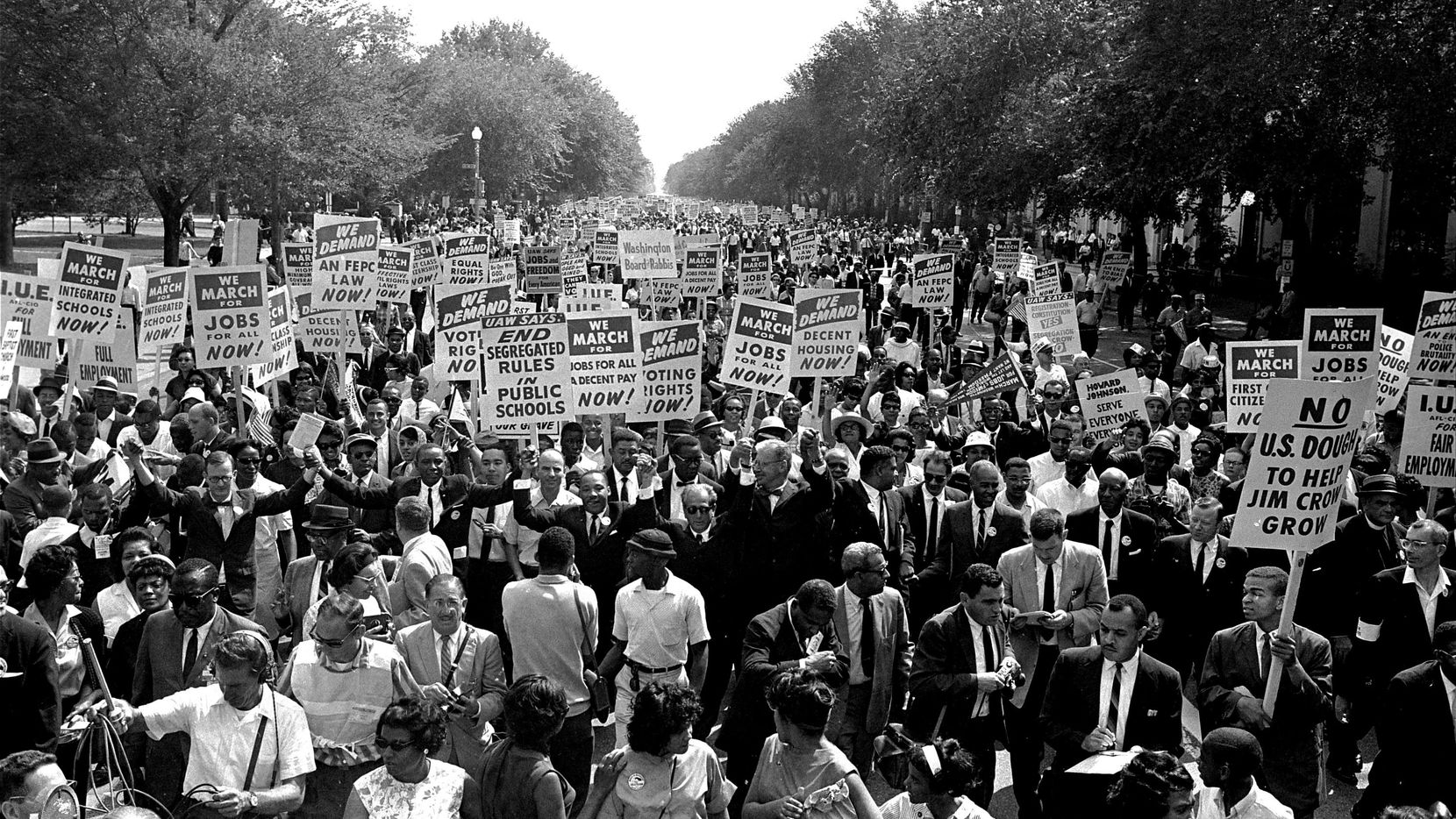 The Rev. Martin Luther King Jr. (center left with arms raised) marches along Constitution Avenue with other civil rights protesters carrying placards, from the Washington Monument to the Lincoln Memorial during the March on Washington on Aug. 28, 1963. (AP Photo)
