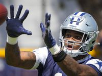 Dallas Cowboys linebacker Micah Parsons (11) reaches for a pass during the first practice of the team's training camp on Thursday, July 22, 2021, in Oxnard, Calif.