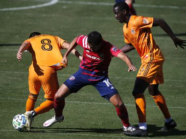 FC Dallas midfielder Andres Ricaurte (10) battles for control of the soccer ball with Houston Dynamo midfielder Memo Rodriguez (8) and Houston Dynamo midfielder Wilfried Zahibo (6) during the first half as FC Dallas hosted the Houston Dynamo at Toyota Stadium in Frisco on Saturday afternoon, October 31, 2020.