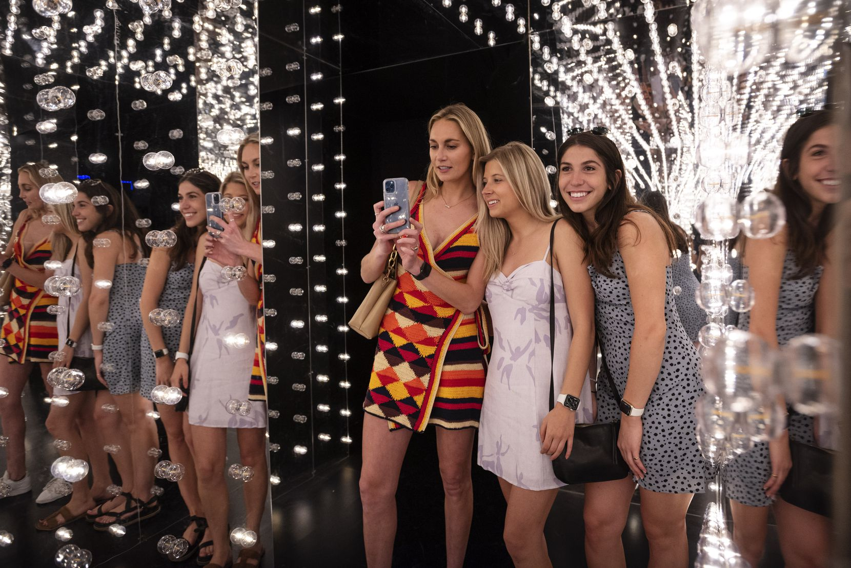Haley Bonneval (from left), Melissa Krumdick and Kate Ferrara pose for photos in a reflective maze at Pop! by Snowday at Galleria Dallas. The installation has more than two dozen scenes where ticket holders can take fun selfies and lively group shots.