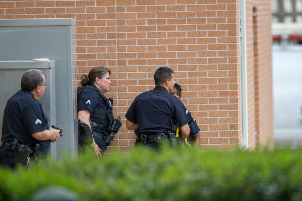 Dallas police officers -- one with his gun drawn -- respond to a report of a threat at the Dallas Police Headquarters on July 9, 2016 in Dallas. (Ting Shen/The Dallas Morning News)