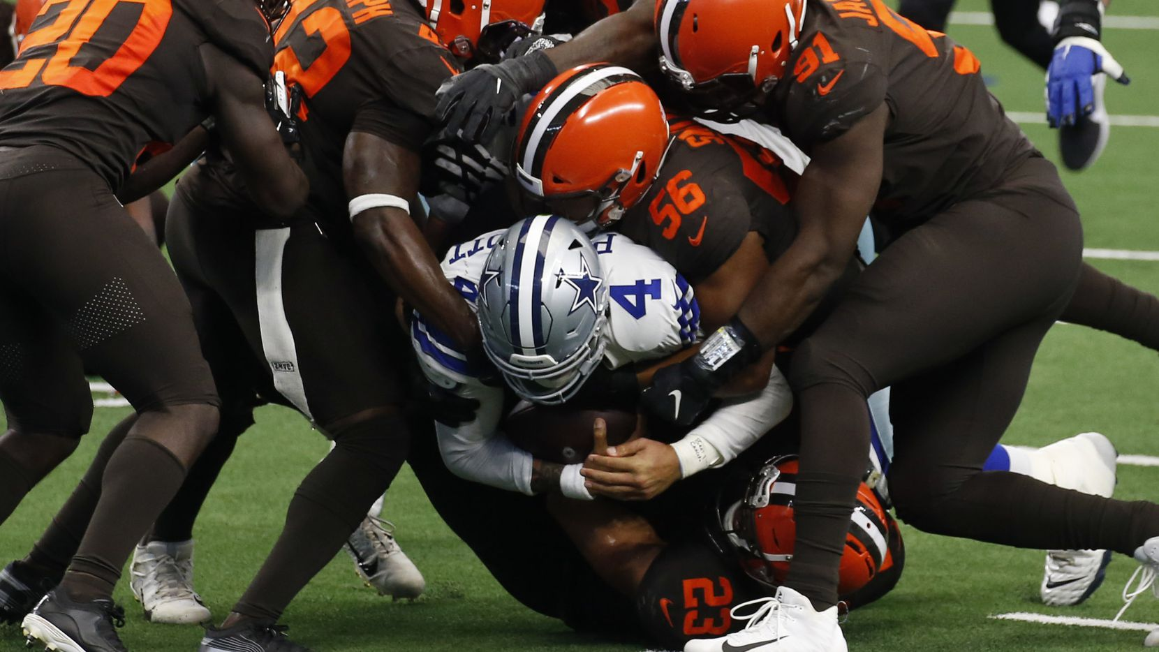 El mariscal de los Dallas Cowboys, Dak Prescott (4), es sepultado por la defensiva de los Cleveland Browns en el partido efectuado el 4 de octubre de 2020 en el AT&T Stadium de Arlington.