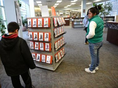 Balda Aguilar and her son Jesus Aguilar, 9, look at a rack of stories on individual mp3 players at the Mesquite Main Library.