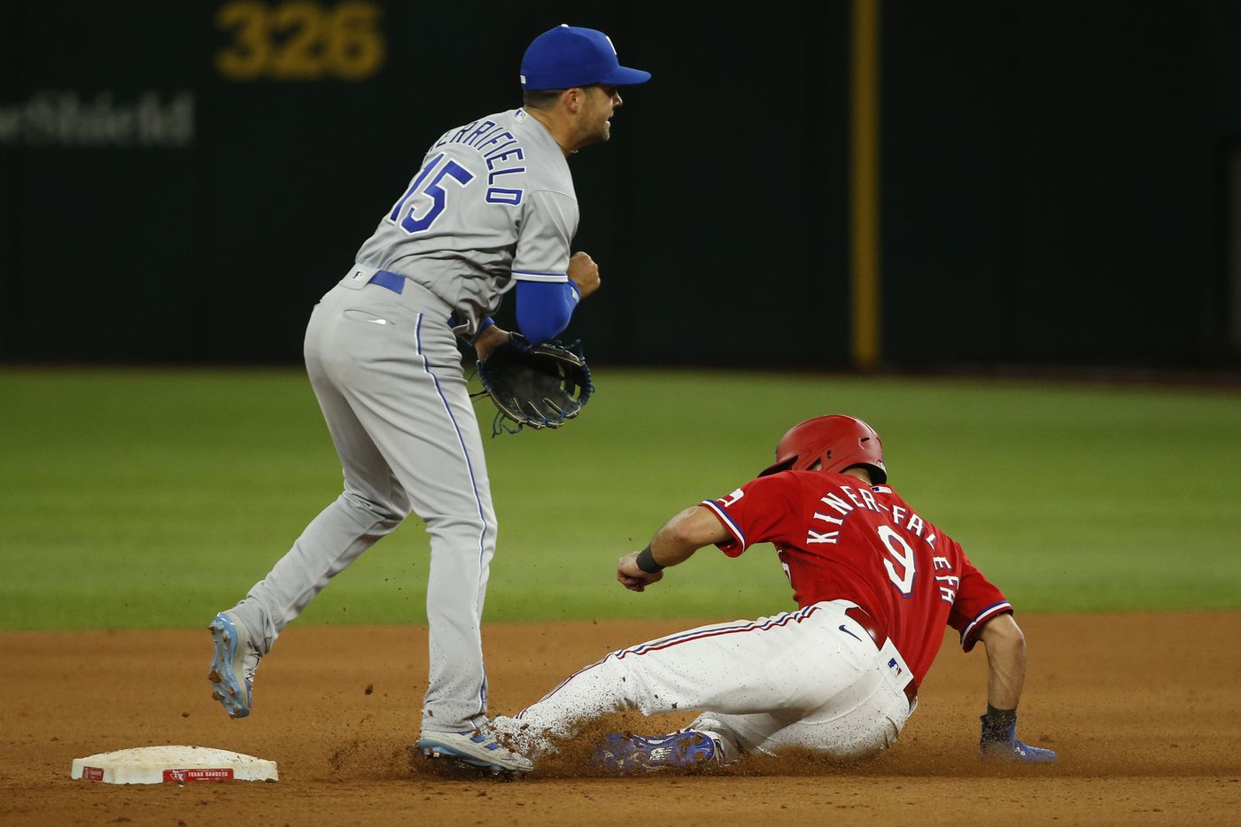 Kansas City Royals second baseman Whit Merrifield (15) starts a double play ahead of a sliding Texas Rangers shortstop Isiah Kiner-Falefa (9) during the eighth inning at Globe Life Field on Friday, June 25, 2021, in Arlington. (Elias Valverde II/The Dallas Morning News)