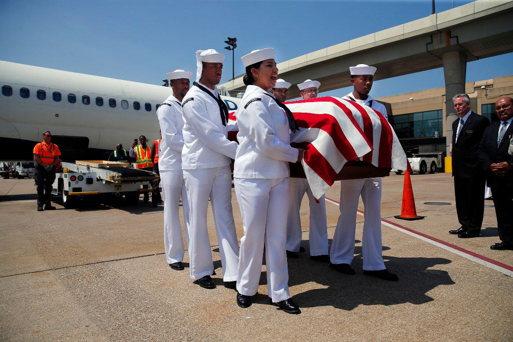 The remains of Navy Seaman 1st  Class (E3) George A. Coke Jr. of Arlington are carried from a commercial flight by members of the NAS JRB Navy Honor Guard to a waiting hearse at Dallas-Fort Worth International Airport, Friday, June 23, 2017. Coke, who perished in the USS Oklahoma after it sank at Pearl Harbor, was identified through recent DNA testing. The North Texas Patriot Guard Riders joined the procession to Moore Funeral Home in Arlington. A service for Coke will be held at First United Methodist Church in central Arlington Saturday before being buried at Parkdale Cemetery.