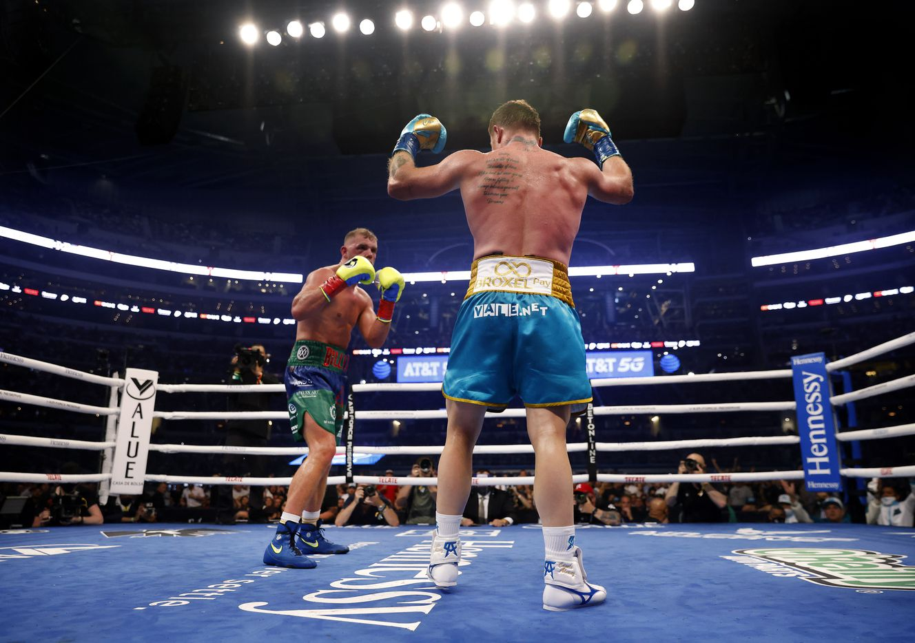 Boxer Canelo Alvarez (right) encourages the crowd to get louder as he has Billy Joe Saunders in his sights during the eighth round of their unified super middleweight title fight at AT&T Stadium in Arlington, Saturday, May 8, 2021. Saunders couldn't go on because he couldn't see following the round. Alvarez won. (Tom Fox/The Dallas Morning News)