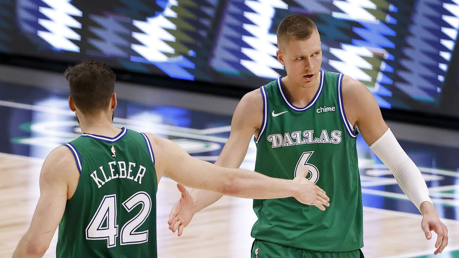 Dallas Mavericks center Kristaps Porzingis (6) is congratulated on his fourth quarter play by teammate Maxi Kleber (42) at the American Airlines Center in Dallas, Thursday, April 8, 2021. The Maverick defeated the Bucks, 116-101.