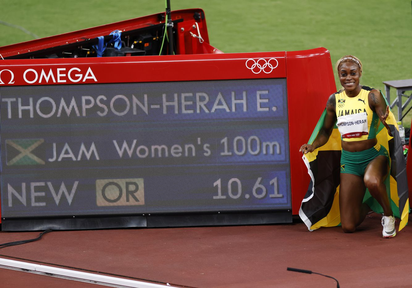 Jamaica's Elaine Thompson-Herah holds up the Jamaican flag after winning the women's 100 meter final race during the postponed 2020 Tokyo Olympics at Olympic Stadium, on Saturday, July 31, 2021, in Tokyo, Japan. Thompson Herah broke the Olympic record with a time of 10.61 to earn a gold medal. (Vernon Bryant/The Dallas Morning News)
