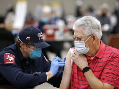 Jim Cox, 79, receives a COVID-19 vaccination from Arlington Fire Lt. Joshua Jones at Esports Stadium Arlington & Expo Center in January. The hub site is distributing over 2,000 vaccinations a day.