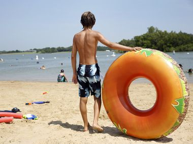 Corbin Clark, 13, of Frisco is ready to hit Lake Lewisville with his inflatable burger as beach goers enjoy the beach at Little Elm Park in Little Elm, Texas, Thursday, July 16, 2020.