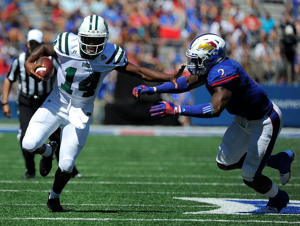 LAWRENCE, KS - SEPTEMBER 10: Quarterback Greg Windham #14 of the Ohio Bobcats slips past Dorance Armstrong Jr. #2 of the Kansas Jayhawks as he runs for a touchdown in the second quarter at Memorial Stadium on September 10, 2016 in Lawrence, Kansas. (Photo by Ed Zurga/Getty Images)