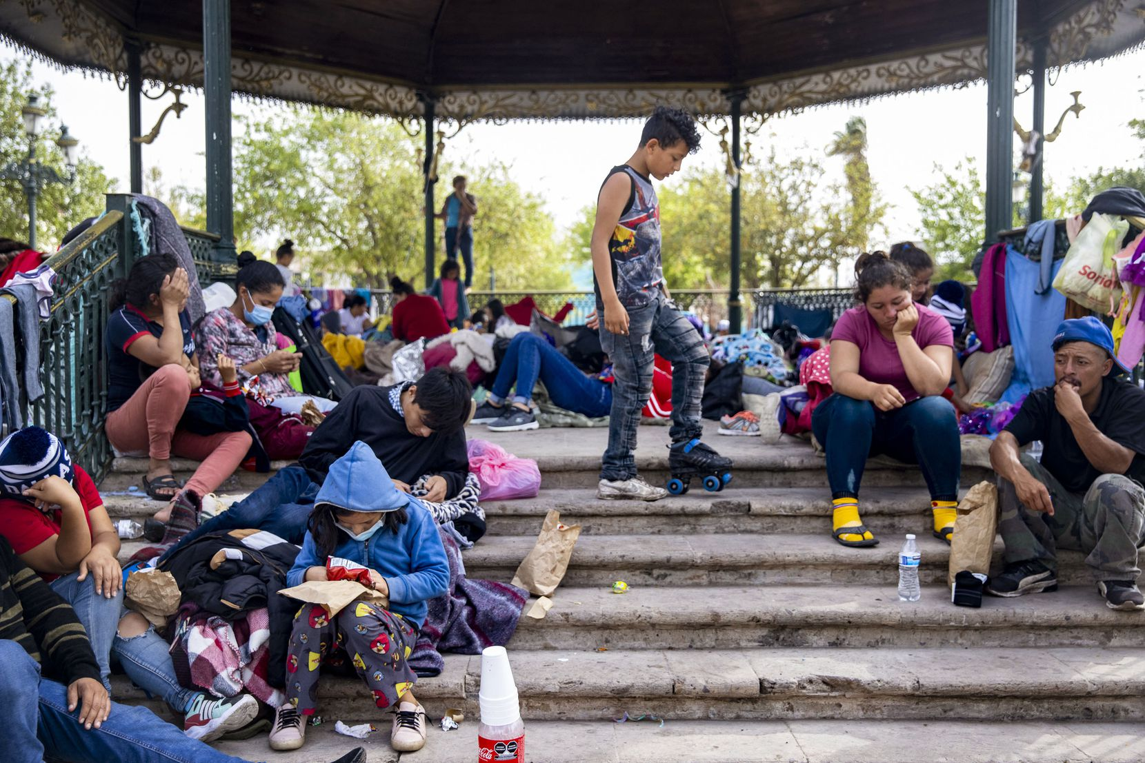 A boy plays with a roller-skate as other expelled migrants sit around a gazebo in a public square in the Mexican border city of Reynosa on Wednesday, March 31, 2021. Migrants have resorted to living at the plaza as the U.S. continues to expel migrants under Title 42 — a pandemic-related public order still in place and left over from the Trump administration.