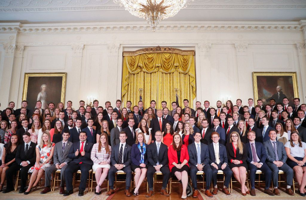 President Donald Trump poses for a photo with outgoing White House interns in the East Room of the White House  (AP Photo/Pablo Martinez Monsivais)