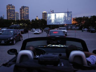 People watch the previews before the show while they visit the Coyote Drive-In in Fort Worth, TX on May 3, 2013. Background is downtown Fort Worth skyline.