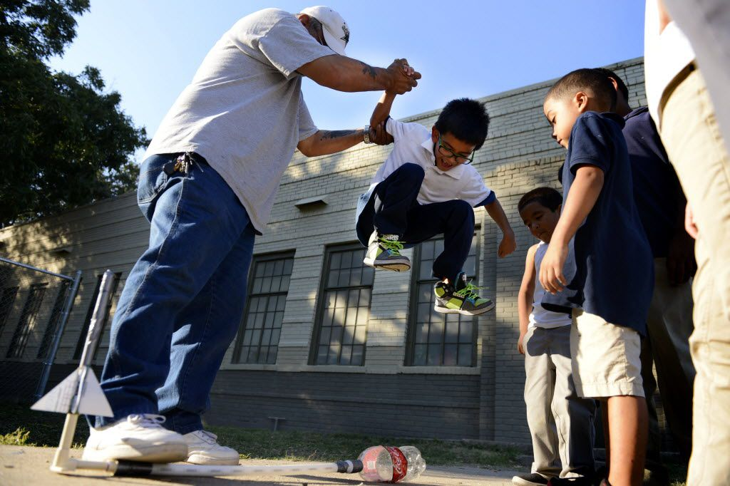 Employee John Sanchez helped Jaiden Martinez, 6, jump on a Coca Cola bottle to release a rocket after school at the Bataan Community Center on Oct. 21, 2014.