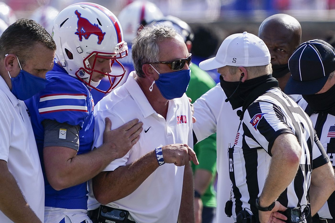SMU head coach Sonny Dykes and quarterback Shane Buechele talk with the referee during the first half of an NCAA football game against Memphis at Ford Stadium on Saturday, Oct. 3, 2020, in Dallas.