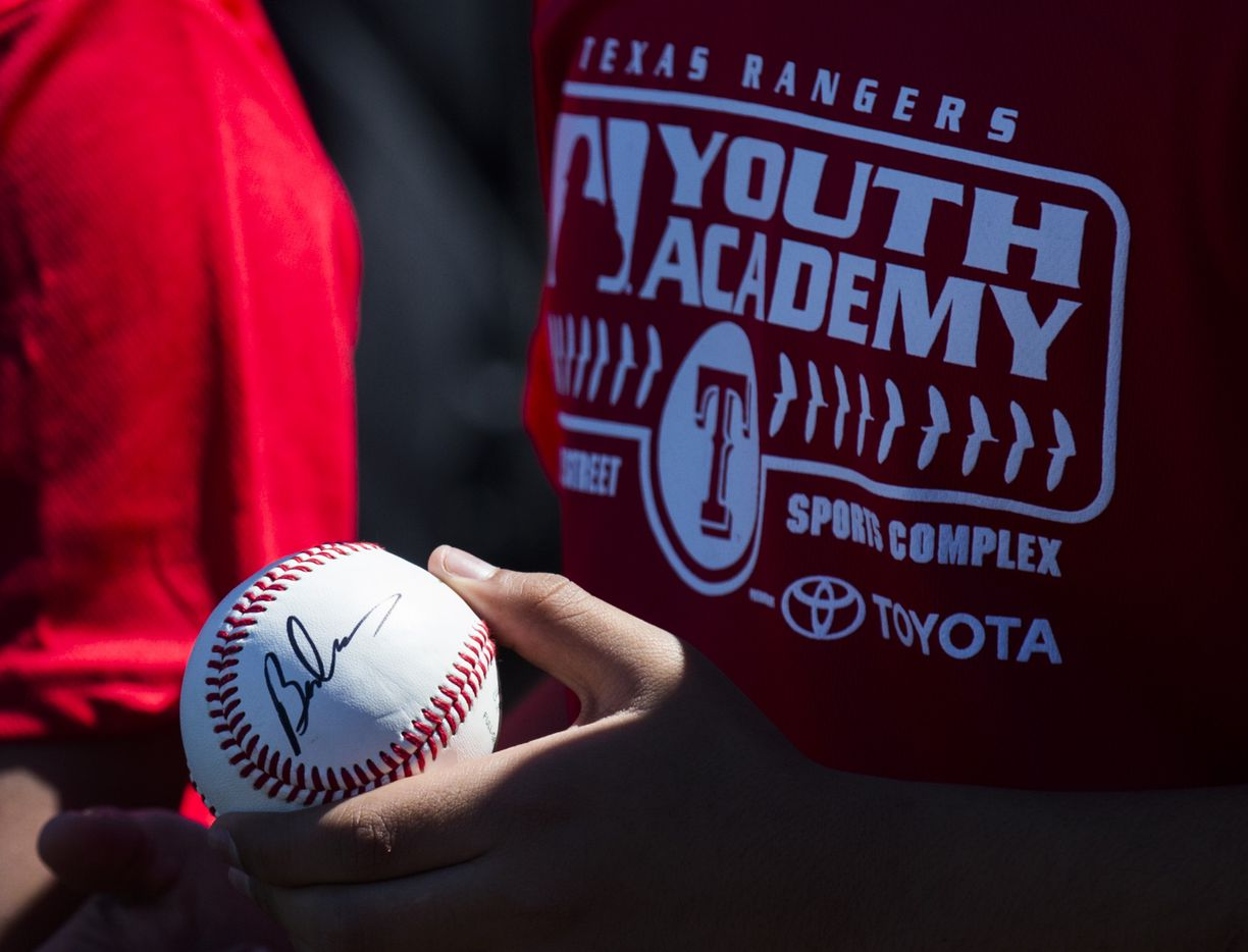 A youth baseball player holds a baseball autographed by U.S. Secretary of Housing and Urban Development Ben Carson that was given to him while Carson took a tour of the Dallas Housing Authority's Major League Baseball Youth Academy. (Ashley Landis/The Dallas Morning News)