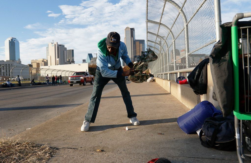 Charles Davis clears off an area on the St. Paul St. overpass of I-30 before laying down his bedding in downtown Dallas at Monday, December 11, 2017. He said he's been on the street for years.  (Ron Baselice/The Dallas Morning News)