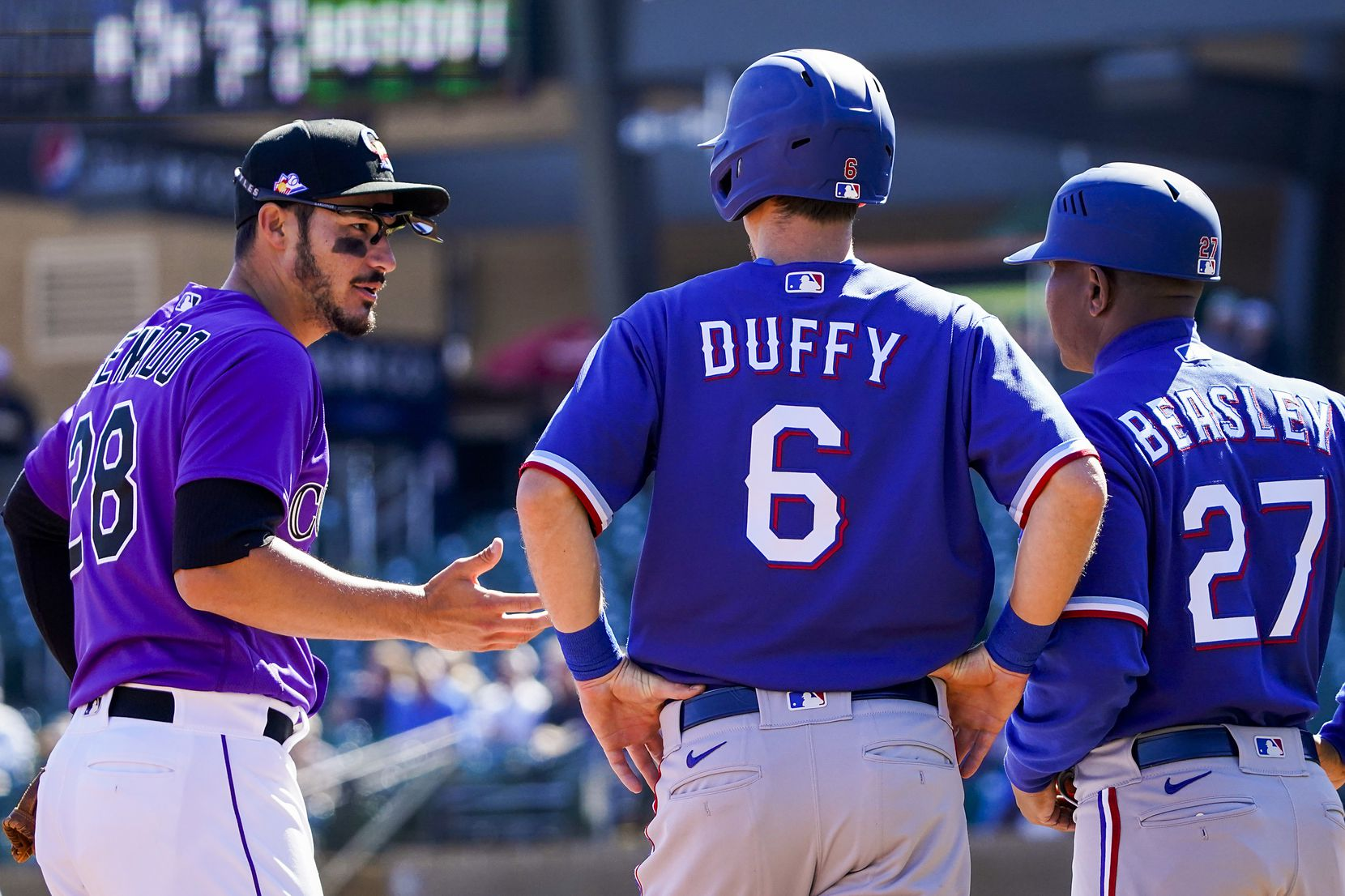 Colorado Rockies third baseman Nolan Arenado chats with Texas Rangers infielder Matt Duffy (6) and third base coach Tony Beasley (27) after Duffy advance from first to third on a double by Scott Heineman during the second inning of a spring training game at Salt River Fields at Talking Stick on Wednesday, Feb. 26, 2020, in Scottsdale, Ariz.