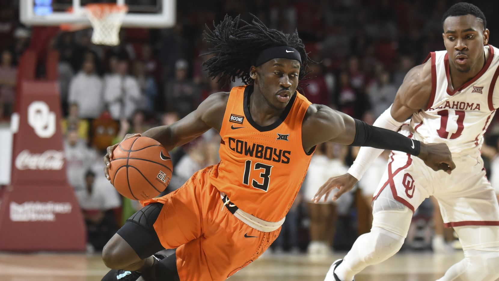 FILE  - In this Feb. 1, 2020, file photo, Oklahoma St. guard Isaac Likekele, left, pushes past Oklahoma guard De'Vion Harmon, right, during the first half of an NCAA college basketball game in Norman, Okla. Likekele, a junior guard, was Oklahoma State's No. 2 scorer last season with 10.9 points per game. (AP Photo/Kyle Phillips, File)