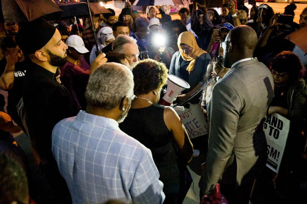 Pastor Michael Waters leads a prayer following a Mothers Against Police Brutality candlelight vigil for Botham Shem Jean at the Jack Evans Police Headquarters on Friday, Sept. 7, in Dallas. Botham Shem Jean was shot by a Dallas police officer who mistook his apartment for hers on Thursday night.