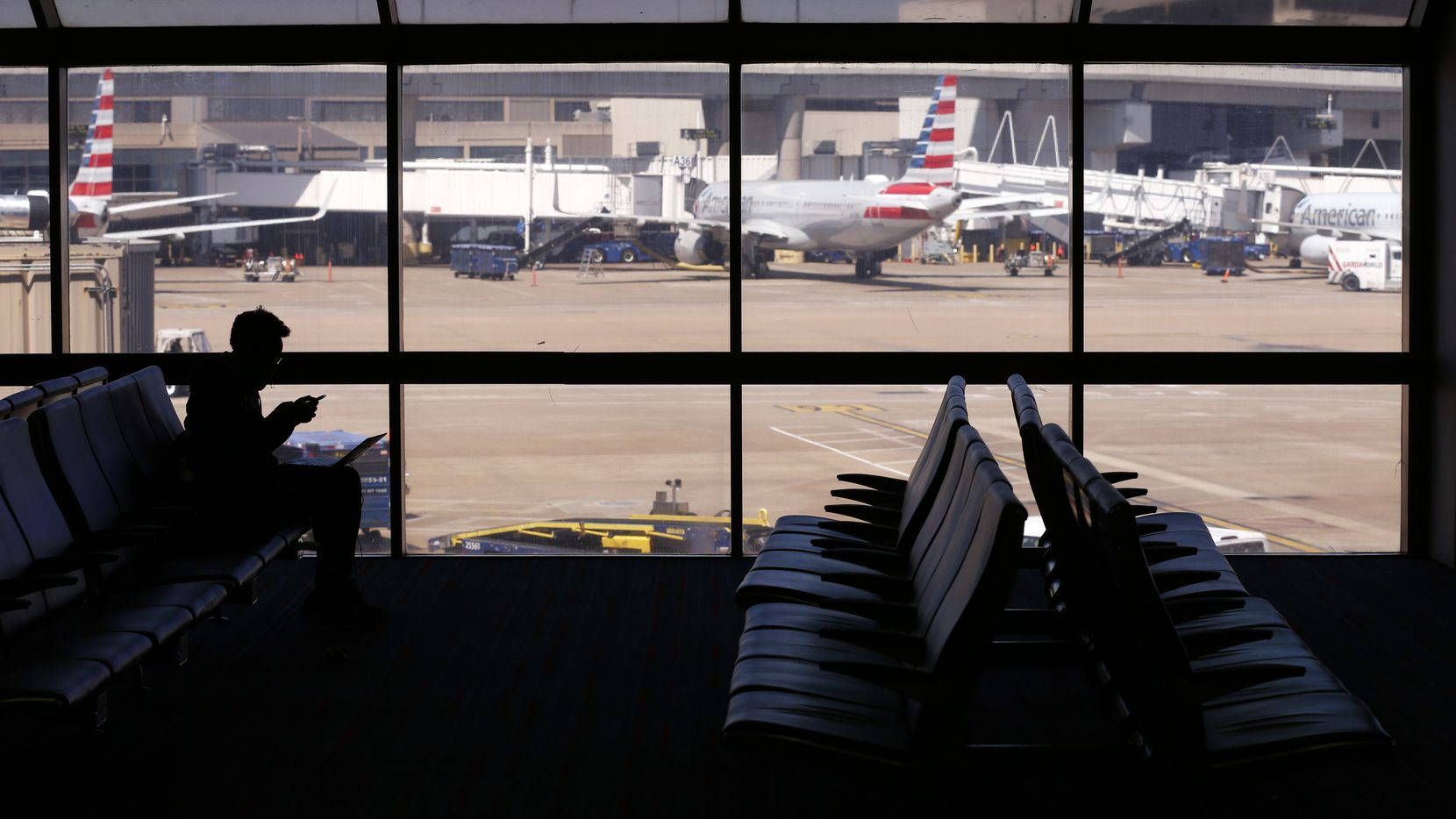 A single traveler sits next to empty chairs at an American Airlines gate in terminal C at DFW International Airport on Wednesday, April 8, 2020. The coronavirus pandemic has made an impact on the travel industry. (Vernon Bryant/The Dallas Morning News)
