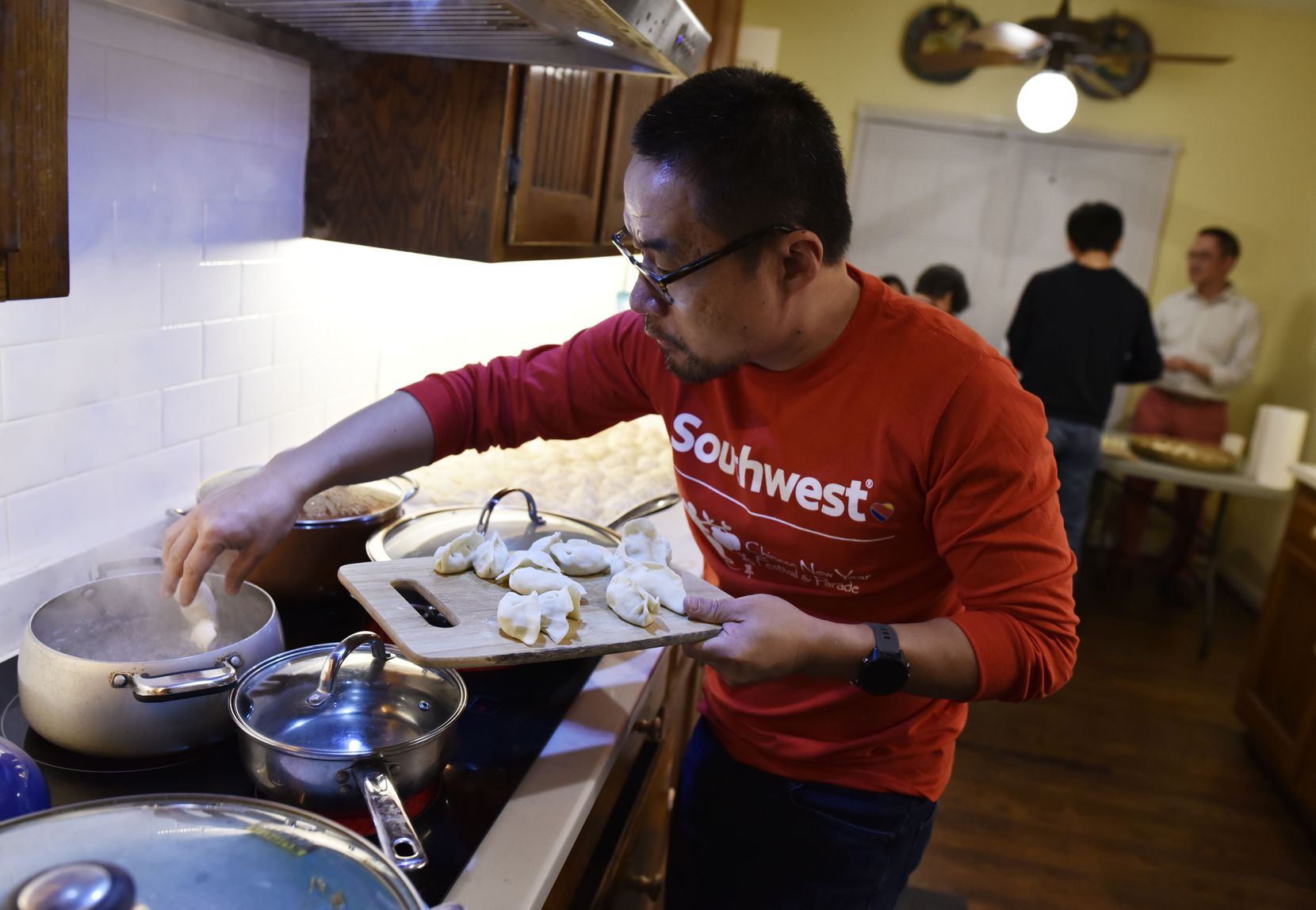 Lin Wang places vegetarian dumplings into boiling water during a Chinese New Year party in Dallas on Saturday Feb. 2, 2020.