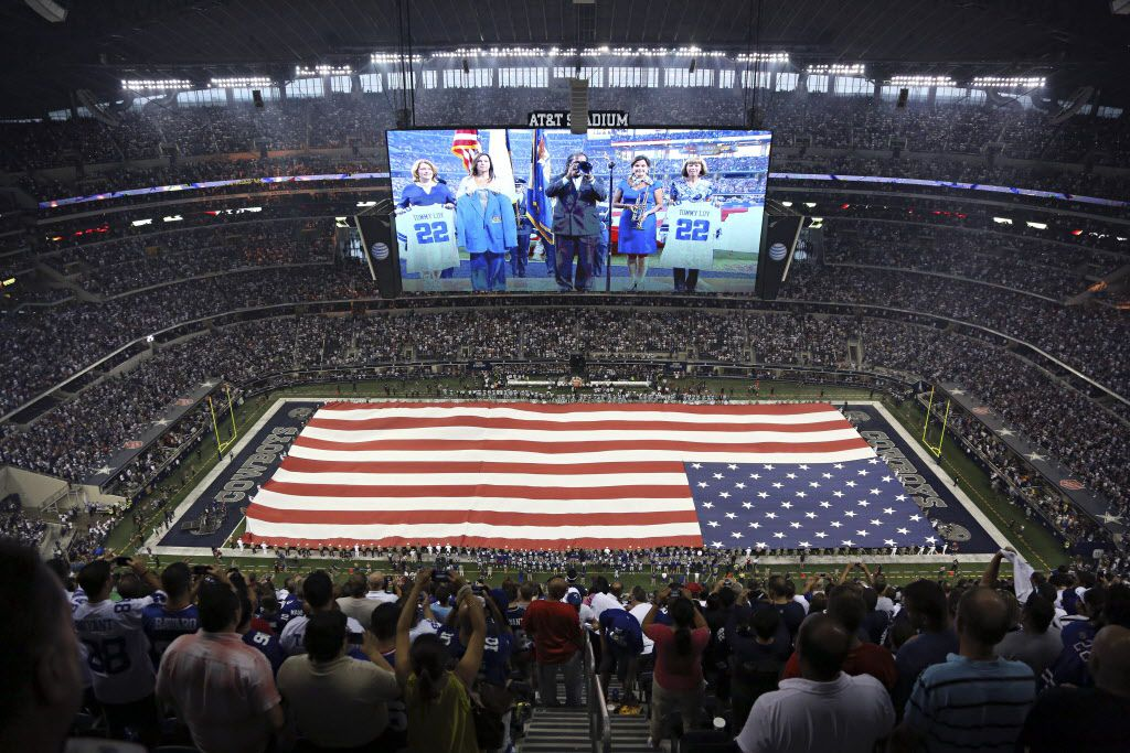 A large American flag is held over the field during the national anthem at the Dallas Cowboys' 36-31 win over the New York Giants Sunday, September 8, 2013 at AT&T Stadium in Arlington.