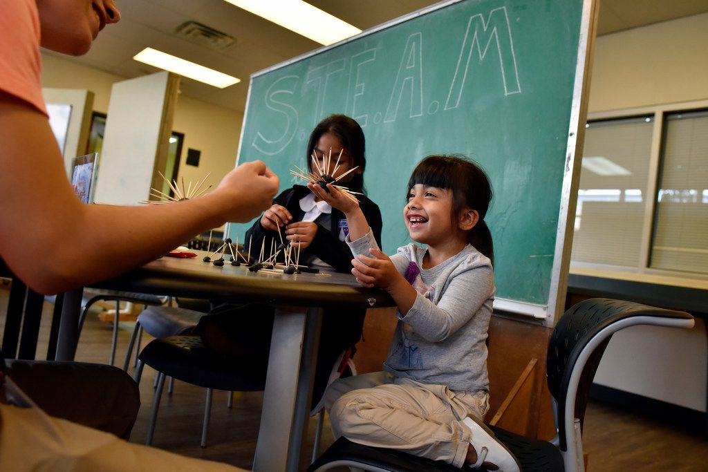 First-grader Layla Puente reacts with a smile as she shows off her creation to tutor Christian Hernandez during a building activity at the Trinity River Mission after school program in West Dallas, Monday, Sept. 10, 2018.