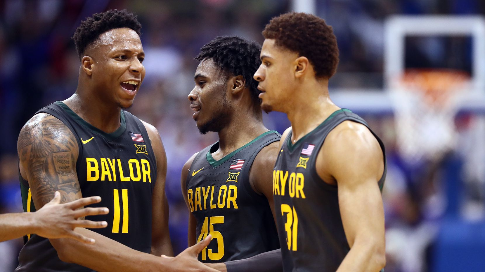 LAWRENCE, KANSAS - JANUARY 11:  Mark Vital #11 and Davion Mitchell #45 of the Baylor Bears congratulate MaCio Teague #31 after a basket during the game against the Kansas Jayhawks at Allen Fieldhouse on January 11, 2020 in Lawrence, Kansas.