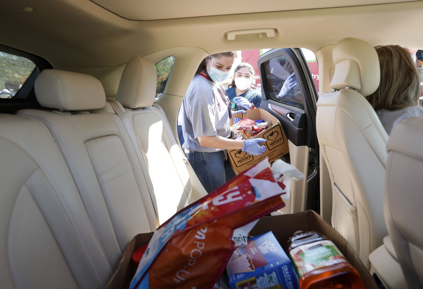 Hannah Nordstrom, a volunteers with Minnie's Food Pantry, loads a car with a meal box filled with groceries for families who are facing food insecurity during the coronavirus outbreak