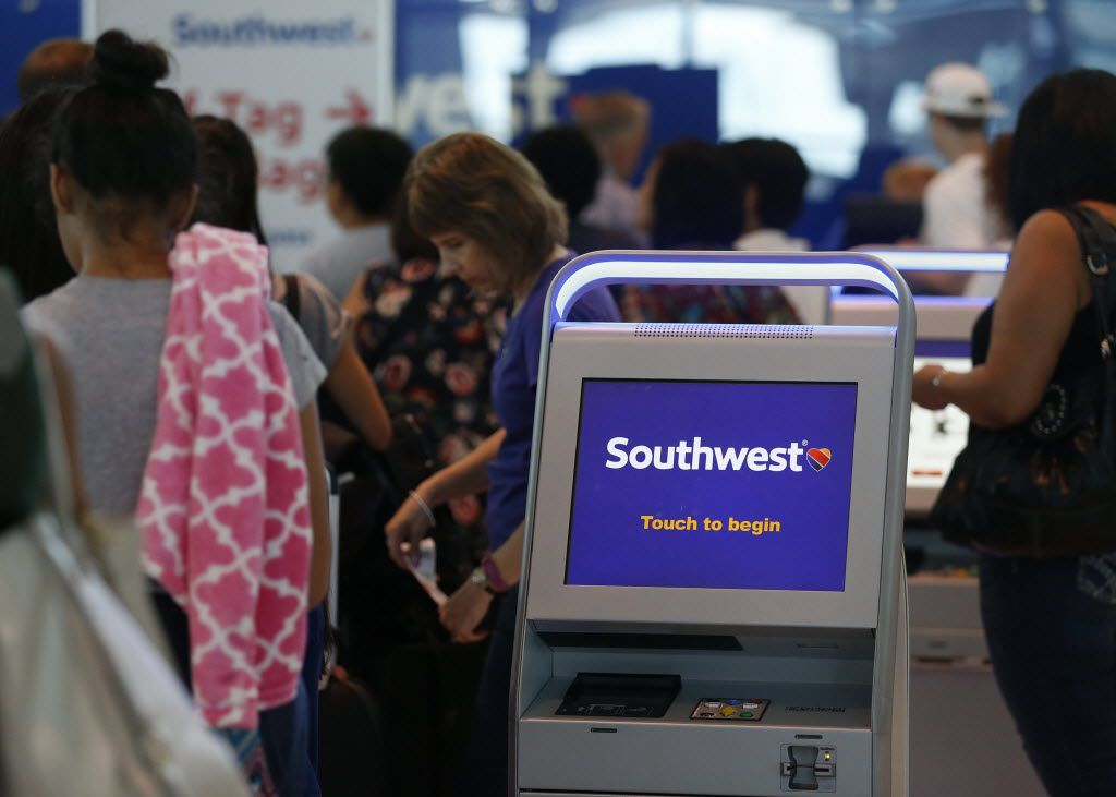 Passengers wait in line at the Southwest Airlines terminal at Dallas Love Field Airport.