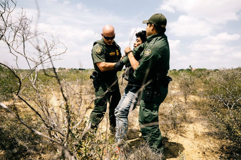 Border Patrol agents Michael Johnson (left) and Christian Salmon apprehend a Honduran national who crossed the Rio Grande in an inflatable raft near Roma. Surveillance towers, drones, helicopters and unmanned blimps are all being used here to build a virtual wall, one which some experts say can be as effective as a physical one, at far lower cost.