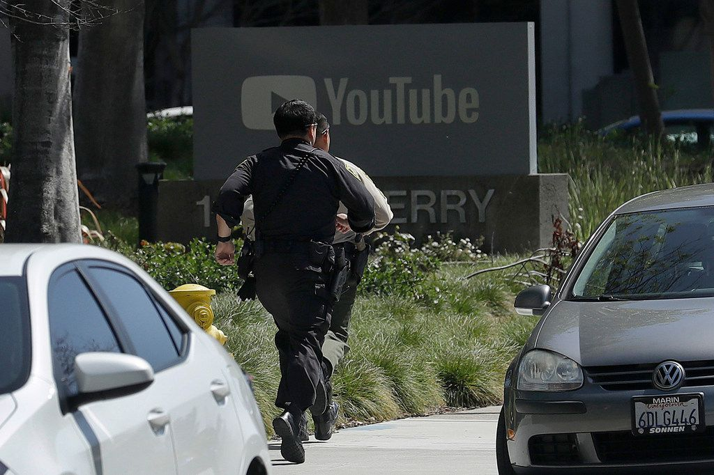 Officers run toward a YouTube office in San Bruno, Calif., on Tuesday.