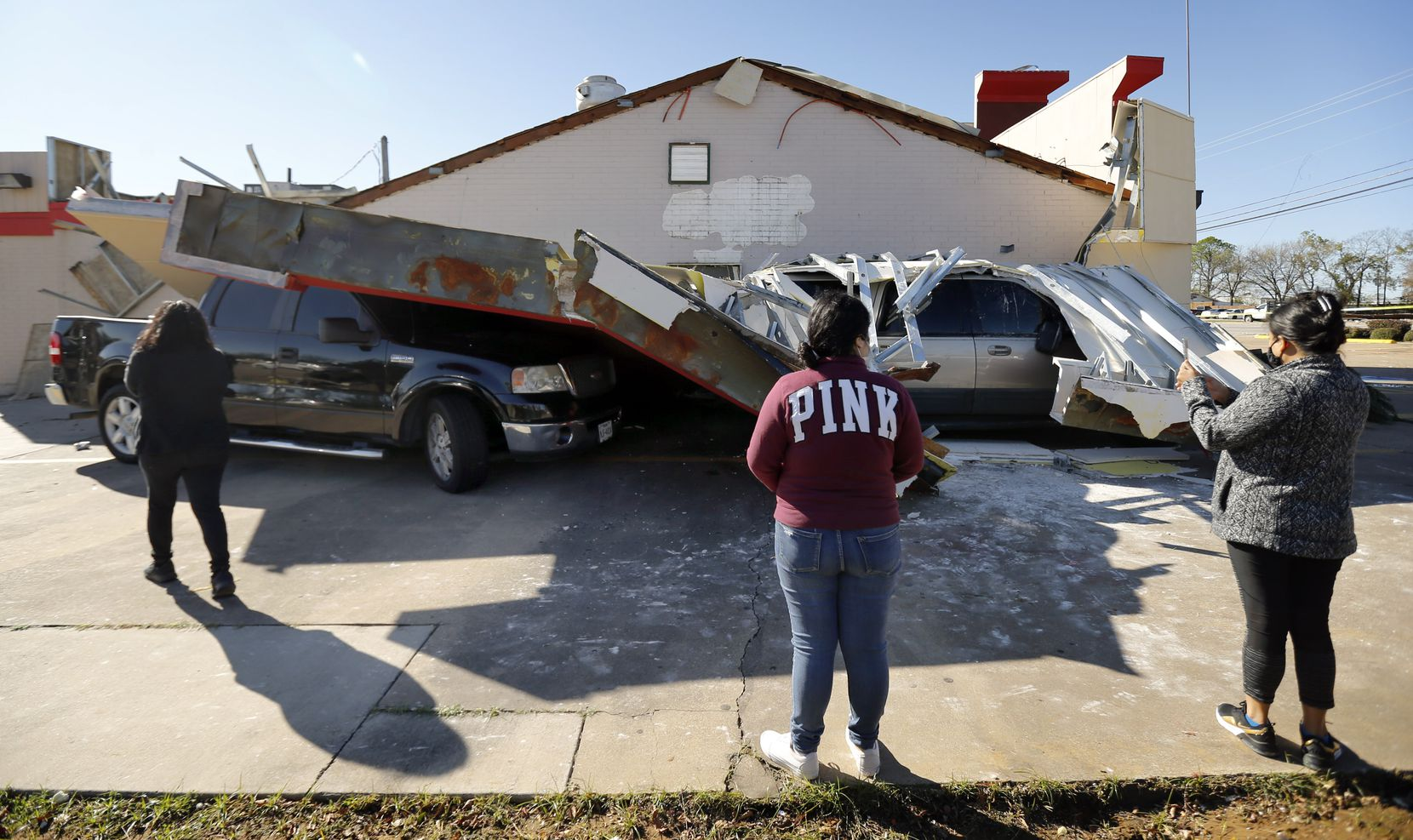 Burger Box restaurant employees (from left) Ana Espinoza, Jennifer Capado, and Maria Espinoza inspect the damage where two customers vehicles were trapped under the drive thru roof awning, Wednesday, November 24, 2020. A tornado-warned storm tore the roof off, trapping the drivers in their vehicles on S. Cooper St.
