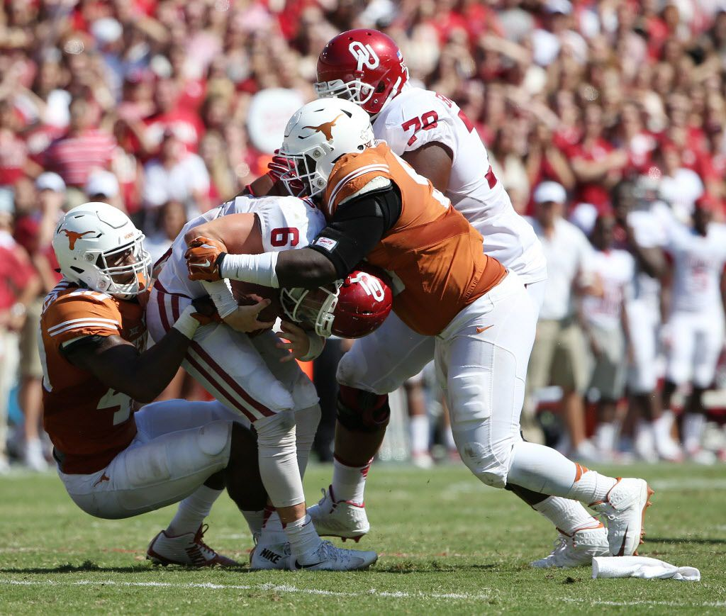 Texas Longhorns defensive end Naashon Hughes (40) and defensive tackle Poona Ford (95) sack Oklahoma Sooners quarterback Baker Mayfield (6) in the fourth quarter during an NCAA football game between Oklahoma and Texas at the Cotton Bowl in Dallas Saturday October 10, 2015. Texas Longhorns beat Oklahoma Sooners 24-17. (Andy Jacobsohn/The Dallas Morning News)