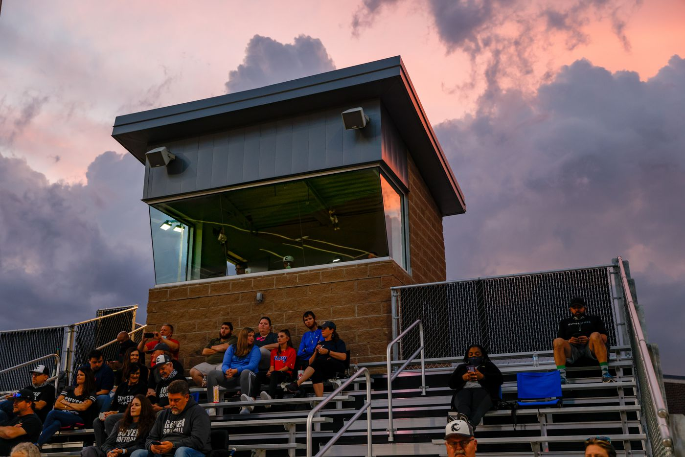 The sun sets as fans watch a nondistrict high school softball game between Denton Guyer and Keller in Denton on Tuesday, March 30, 2021. (Juan Figueroa/ The Dallas Morning News)