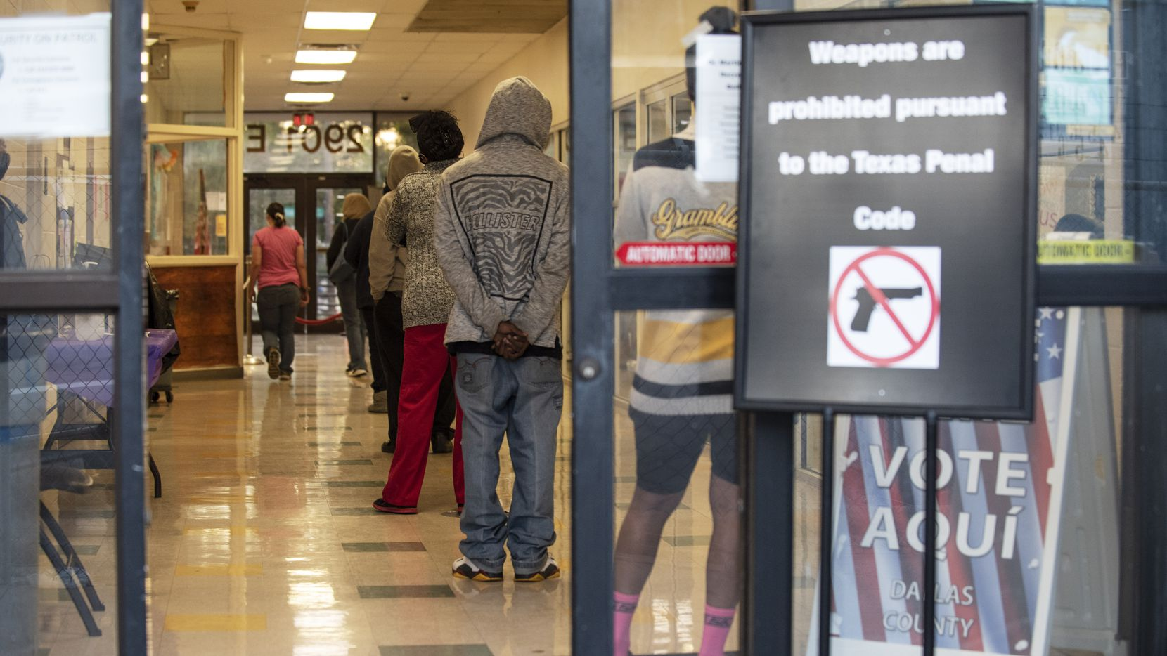 A line of 10 people wait inside a polling location to vote for the 2020 election at the Martin Luther King Jr. Recreation Center in Dallas, on Tuesday, Nov. 03, 2020. A proposed bill at the Texas House would allow election judges to carry handguns at most polling locations.