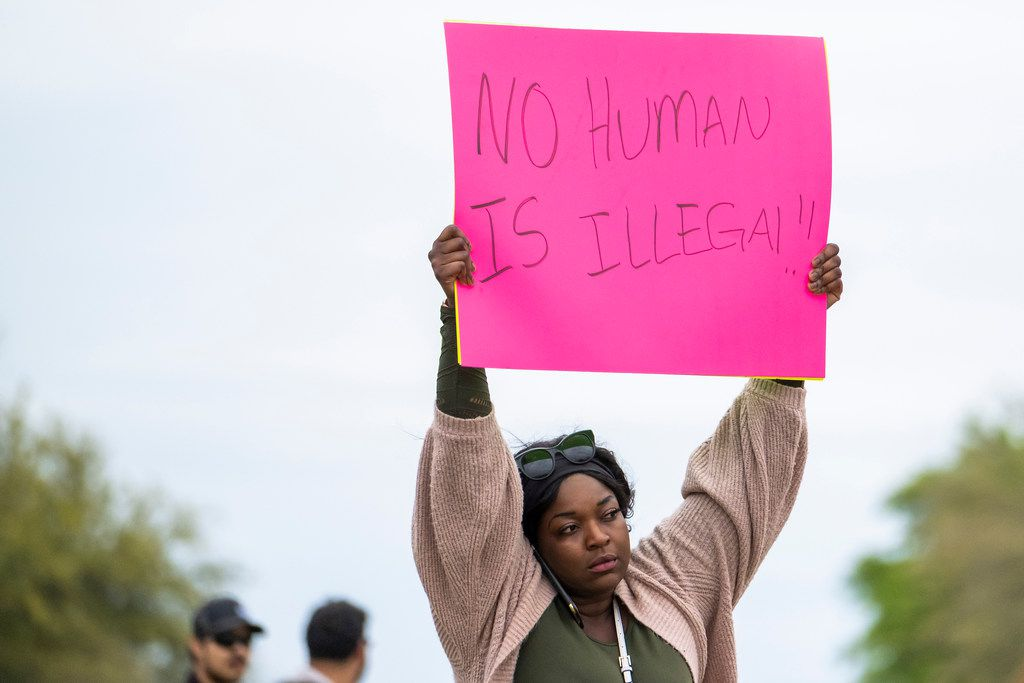 Protesters held signs outside CVE Group in Allen during an ICE operation Wednesday.