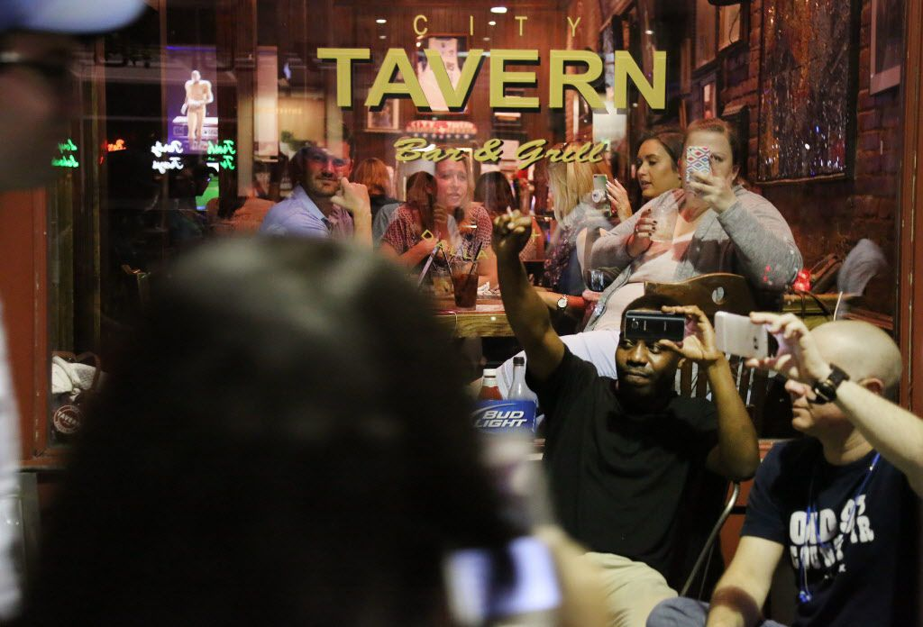 Patrons at the City Tavern react to protesters marching along Main Street during a protest held by the Next Generation Action Network, Thursday, Sept. 22, 2016 in downtown Dallas. Dominique Alexander the leader of the Dallas group behind a July march at which five police officers were killed by a sniper has led a downtown Dallas protest rally the day he left prison. (Andy Jacobsohn/The Dallas Morning News via AP)