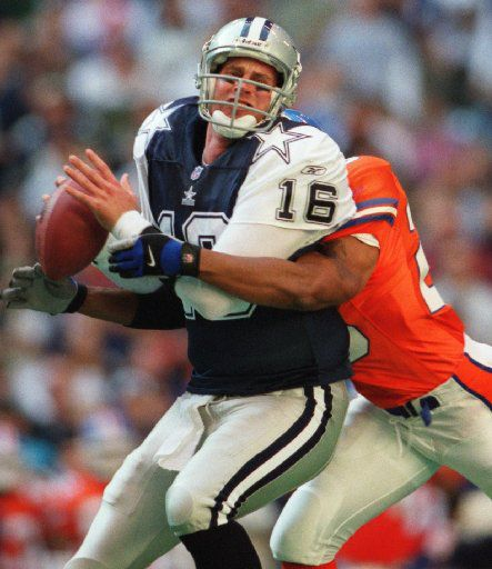 Cowboys quarterback Ryan Leaf #16) feels the crunch of the Denver Bronco defense as he is hit by blitzing Broncos safety Eric Brown (#26) and fumbles on a third and goal situation in first quarter action at Texas Stadium Thursday afternoon. Dallas recovered the fumble which resulted in the Cowboys having to settle for a field goal to tie the game at 3-3.