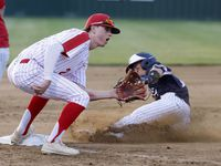 Allen's Tim Regnolds steals third in front of Flower Mound Marcus third baseman Ty Johnson during the 2nd inning of a Class 6A bi-district baseball playoff game in Flower Mound, Texas on April 7, 2021.