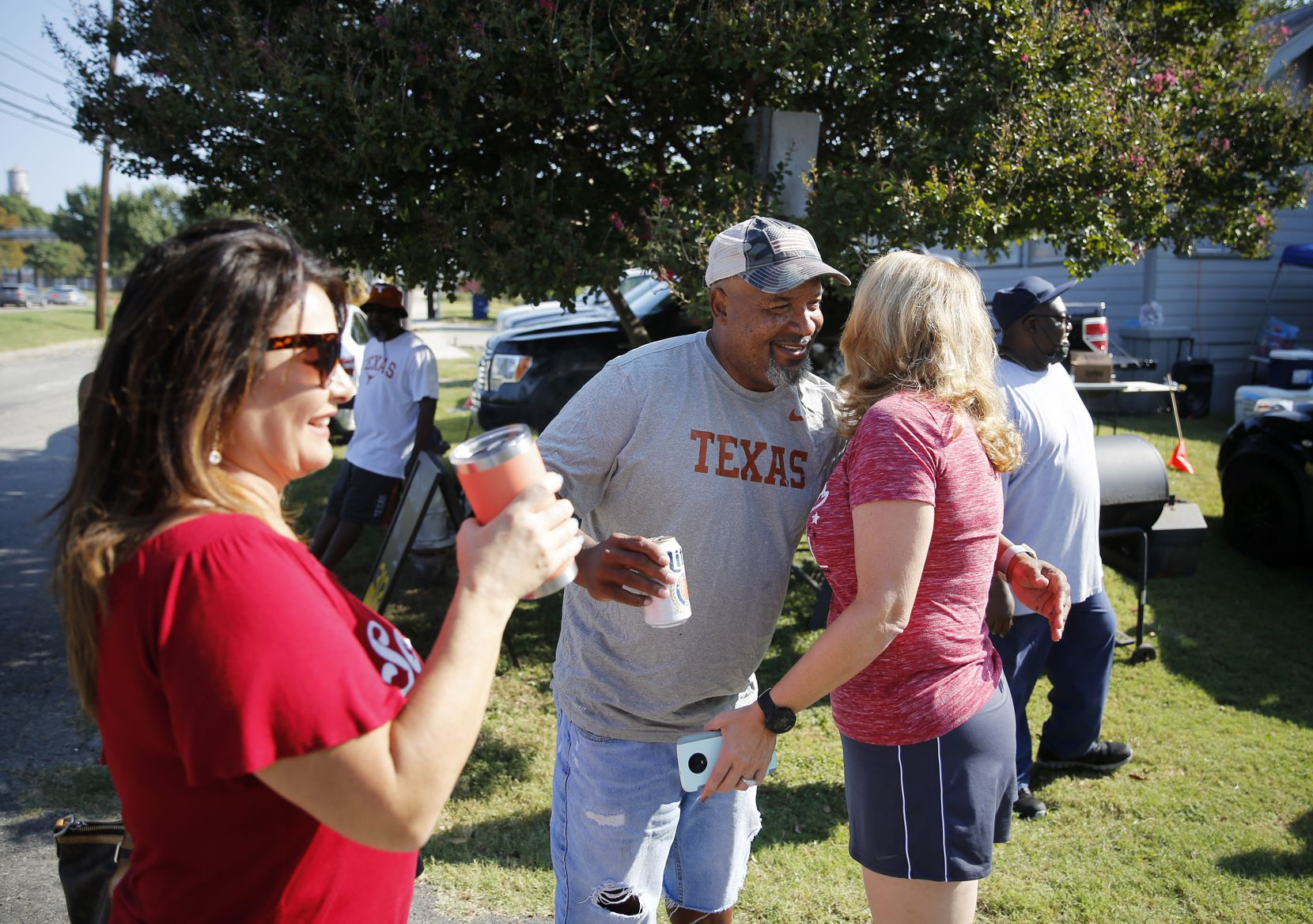 Stacey Walker of Dallas greets Barbara Brockhaus (right) of Oklahoma City and Bethany Neighbors (left) of Oklahoma City as they arrive in Dallas on Saturday, October 10, 2020. Walker, a UT fan, is cooking in preparation for Oklahoma fans he sees annually during the Texas Oklahoma game. They have met up for over a decade. Although the grill masters are diehard fans of their respective teams, the game has turned them into unlikely friends, and over the years, family. (Vernon Bryant/The Dallas Morning News)