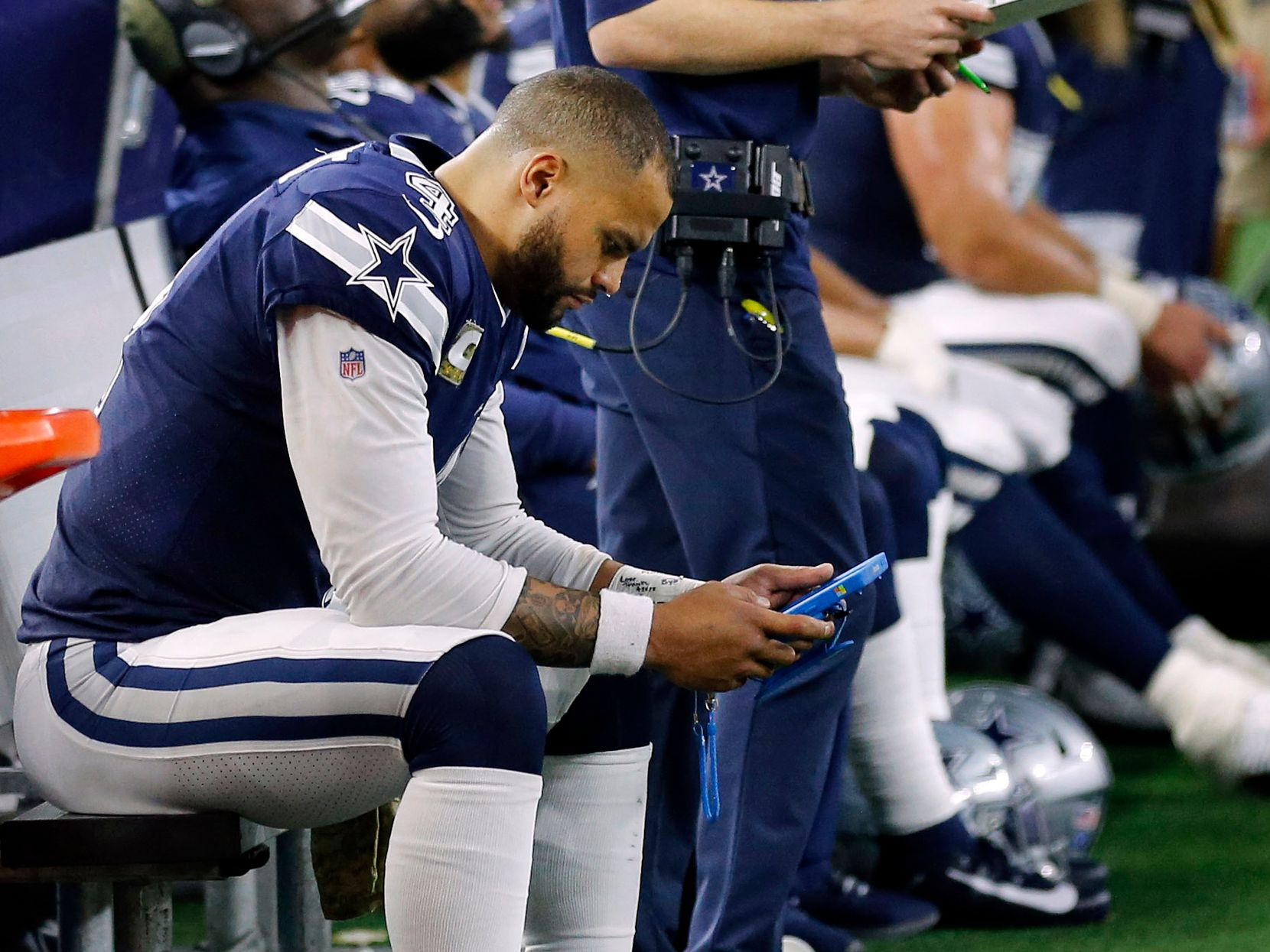 Dallas Cowboys quarterback Dak Prescott (4) looks at a tablet on the bench after he couldn't convert a fourth down play late in the fourth quarter against the Minnesota Vikings at AT&T Stadium in Arlington, Texas, Sunday, November 10, 2019. Offensive coordinator Kellen Moore looks at the video board. (Tom Fox/The Dallas Morning News)