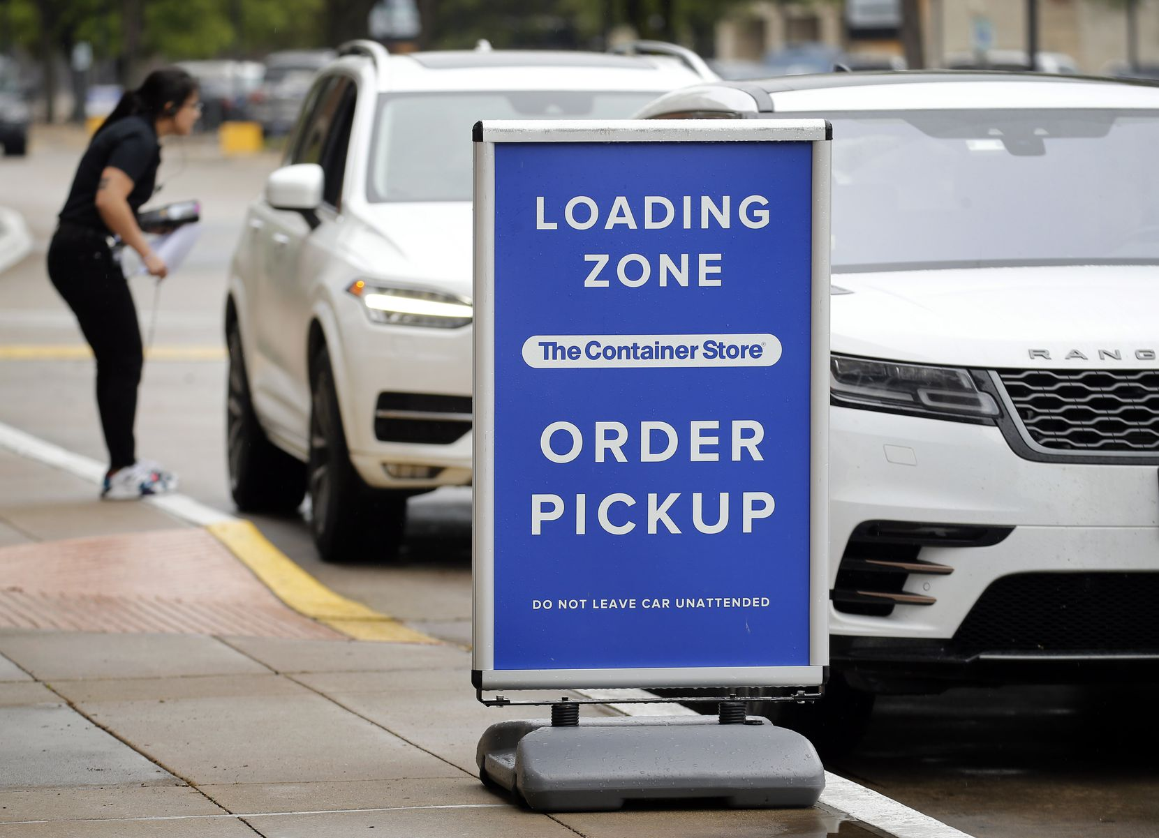 An employee of The Container Store speaks to a customer waiting in the curbside pickup line, Saturday, April 4, 2020, across from NorthPark Center in Dallas,
