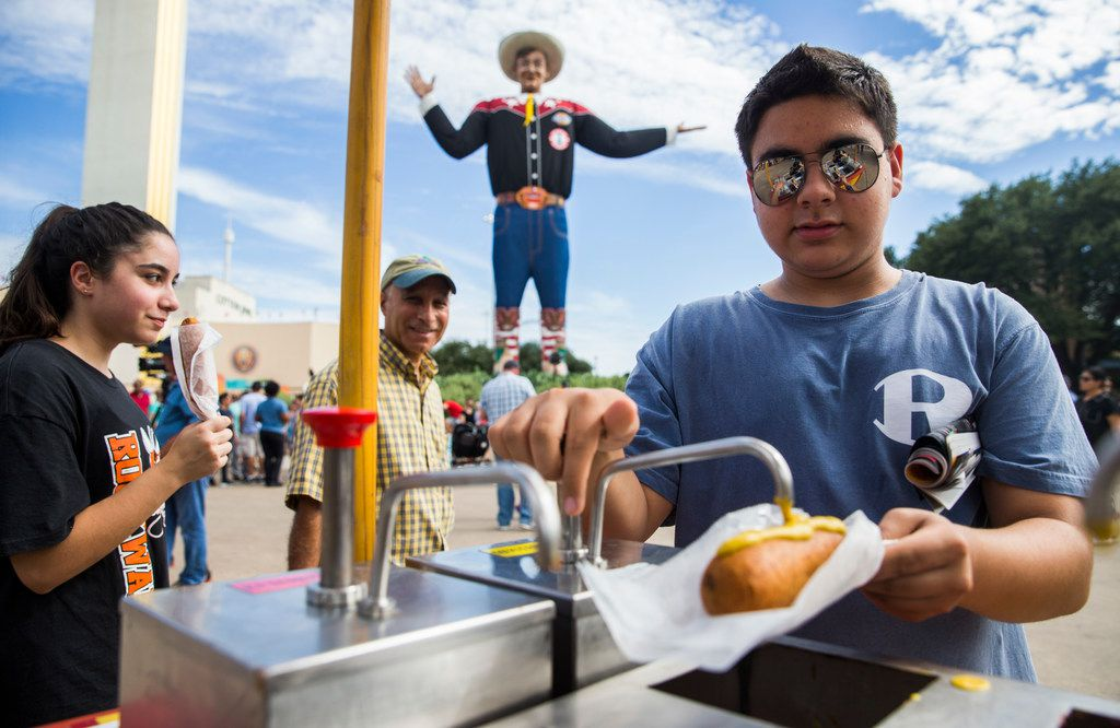 Matthew Kianpour, 15, of Rockwall tops his Fletcher's Corny Dog with mustard on Wednesday, October 4, 2017 at the State Fair of Texas in Dallas.