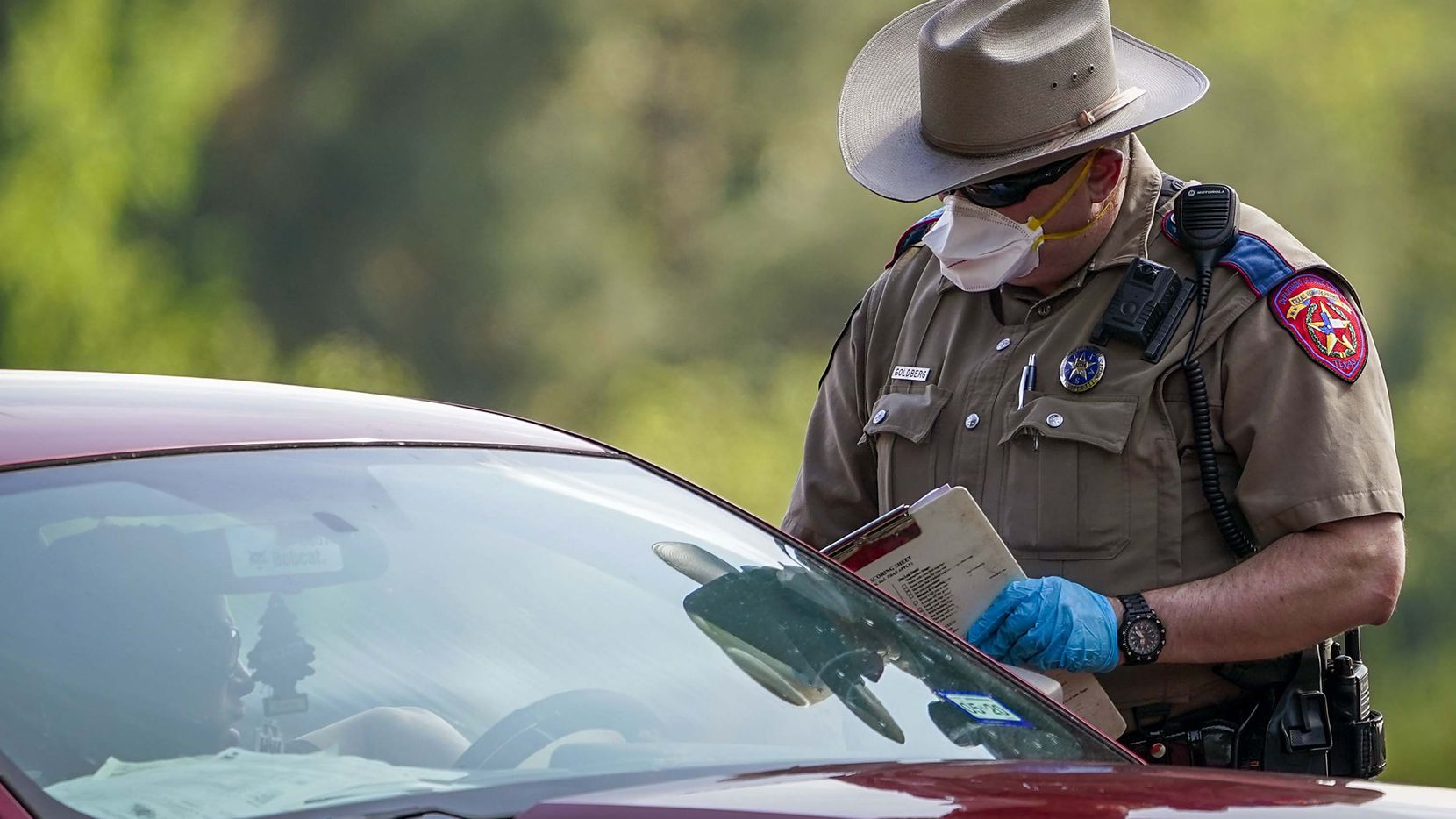 "A Texas Department of Public Safety State trooper talks with a motorist at a checkpoint on I-20 about seven miles west of the Louisiana state line near Waskom, Texas on Tuesday. The department is ""increasing its presence"" on the ground near the Texas-Louisiana border to enforce a 10-day-old, coronavirus quarantine order for road travelers arriving from the Bayou State."